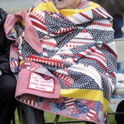 Bill Helm is wrapped in a quilt presented to him during a Memorial Day Service at the Sidney town office on Monday.