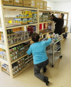 Laverne Pelletier, left, stacks cans on shelves at the Belgrade-Rome Special Needs Food Pantry on Oct. 29, 2015, in Belgrade. The group is among several in central Maine that uses federal funding that's available under the federal Emergency Food and Shelter National Board program.
