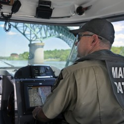 Marine Patrol Officer Clint Thompson patrols the Kennebec River on Tuesday beneath Memorial Bridge in Augusta. Officers from the agency that protects tidal water are checking boaters for safety equipment.