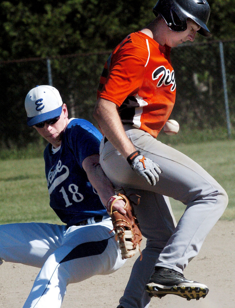 Gardiner runner Logan Peacock makes it back to first base as Erskine's Caleb Barden loses the ball during a Kennebec Valley Conference Class B game Tuesday in Gardiner.