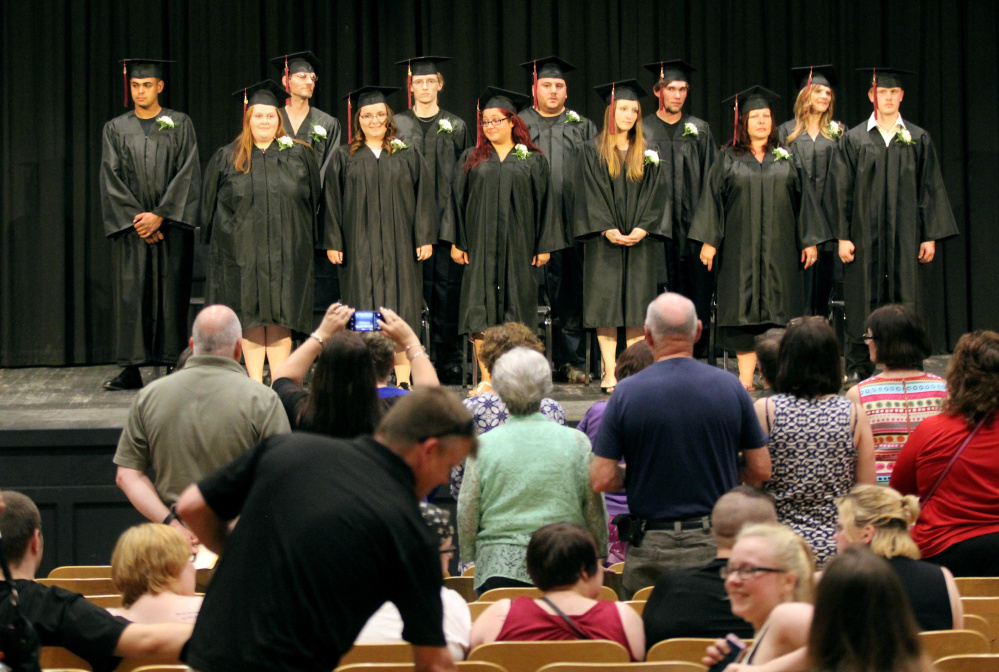 Soon-to-be graduates of Mid-Maine Regional Adult Community Education stand before family and friends at the beginning of the graduation ceremony Tuesday night at Trask Auditorium at Waterville Senior High School.