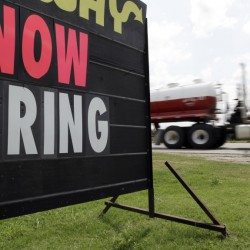 "An oil truck passes a ""now hiring"" sign in Kennedy, Texas. With the Federal Reserve edging into the spotlight, the Friday jobs report could trigger changes in Americans' financial lives."