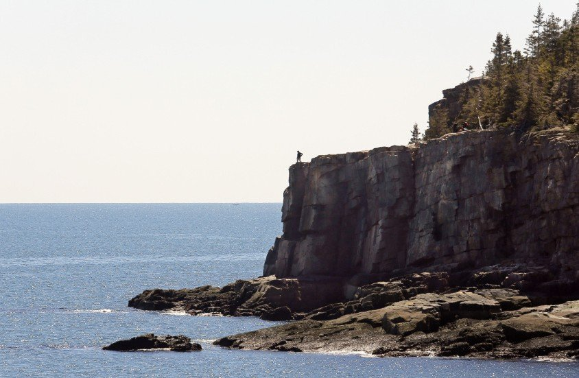 A visitor looks out over the ocean from Otter Cliffs in Acadia National Park. Numerous locals take advantage of the quiet shoulder seasons in spring and fall, when the crowds are absent from the park.