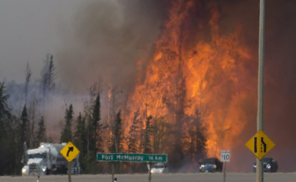 Heat waves are seen as cars and trucks try to get past a wildfire south of Fort McMurray, Alberta, on Friday.