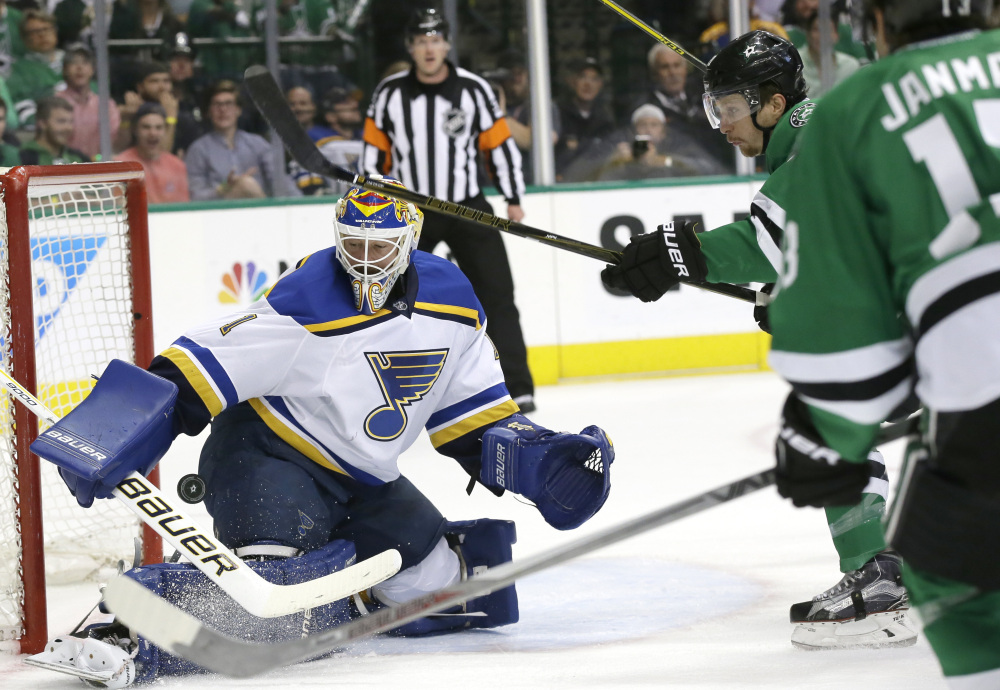 Blues goalie Brian Elliott defends the goal against Dallas left wing Antoine Roussel, 21, and center Mattias Janmark in the first period of Game 5 of the Western Conference semifinals Saturday in Dallas.