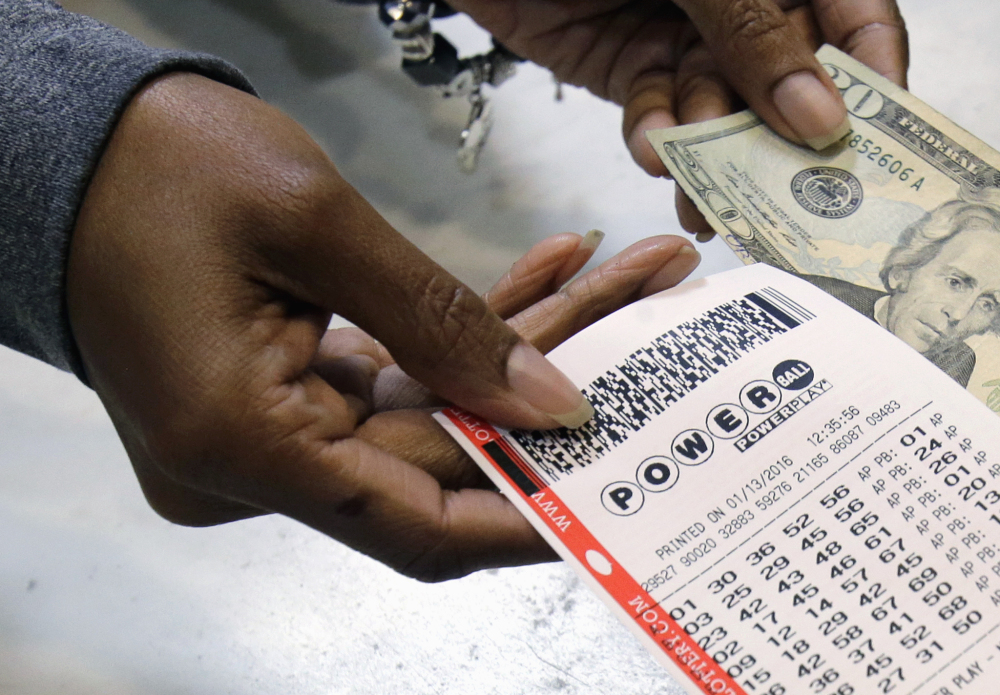 A clerk hands  a Powerball ticket to a customer.