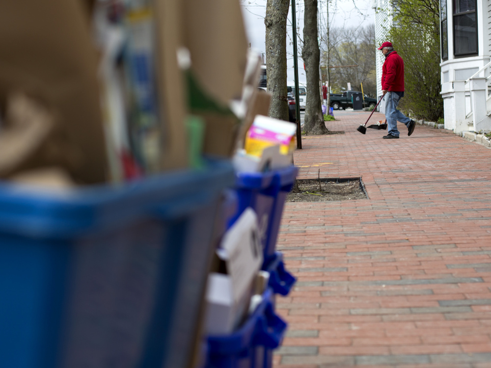 Cliff Bernard sweeps up litter on Bramhall Street last week. Bernard says he is subcontracted by Maine Medical Center to keep surrounding streets clean, a job made challenging on trash and recycling day. Derek Davis / Staff Photographer