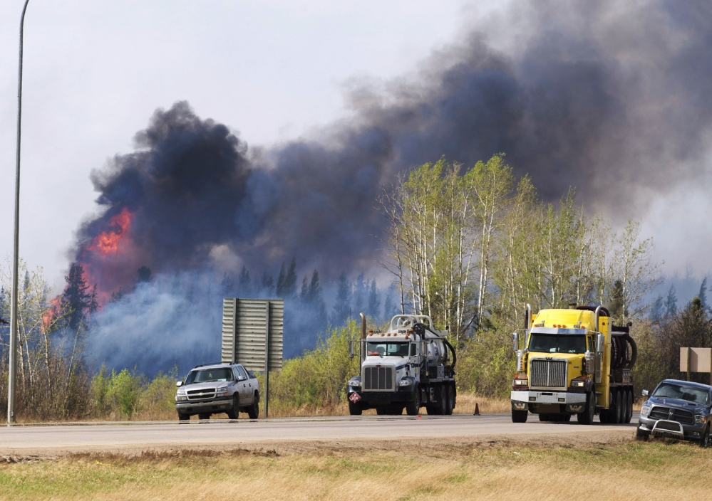 Flames flare up from hot spots along the highway to Fort McMurray in Alberta on Sunday. Ryan Remiorz/The Canadian Press via AP