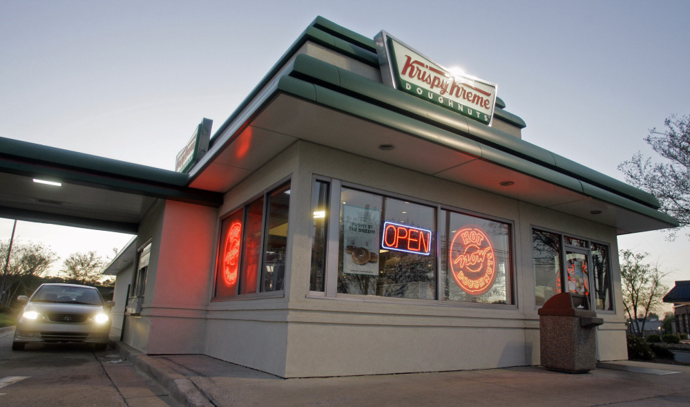 A customer picks up doughnuts at the drive through at a Krispy Kreme store in Matthews, N.C. Krispy Kreme is being taken private by JAB Beech in a deal announced Monday.