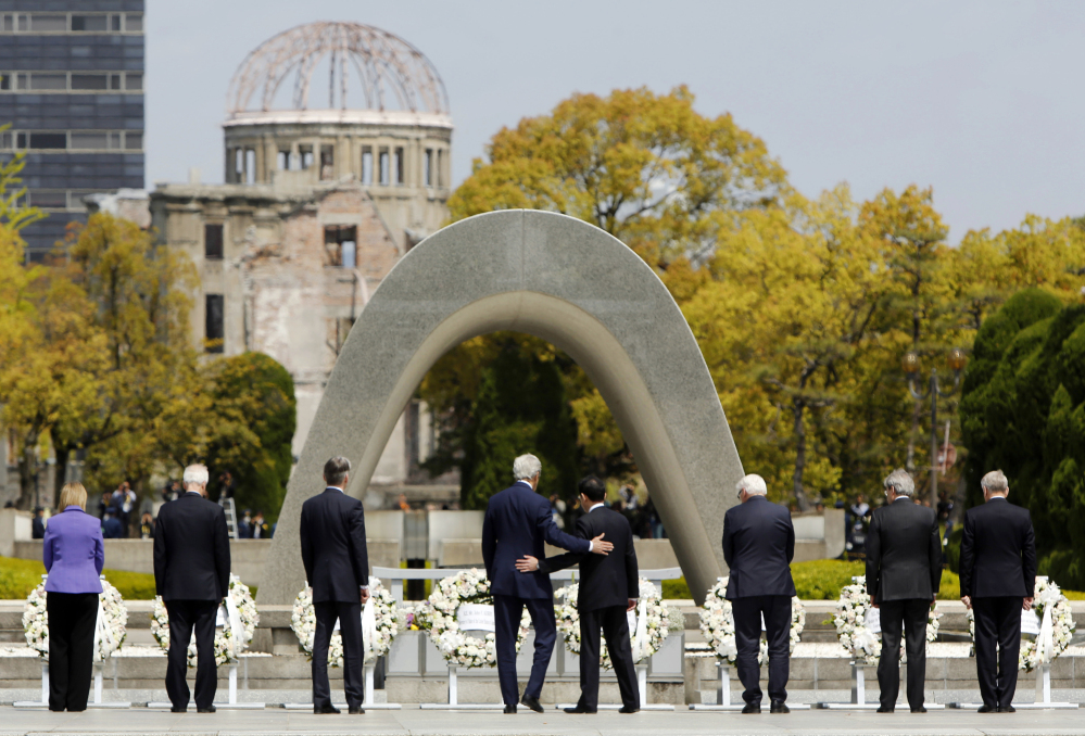 U.S. Secretary of State John Kerry (center L) puts his arm around Japan's Foreign Minister Fumio Kishida (center R) after they and fellow G7 foreign ministers laid wreaths at the cenotaph at Hiroshima Peace Memorial Park and Museum in Hiroshima, Japan April 11, 2016.