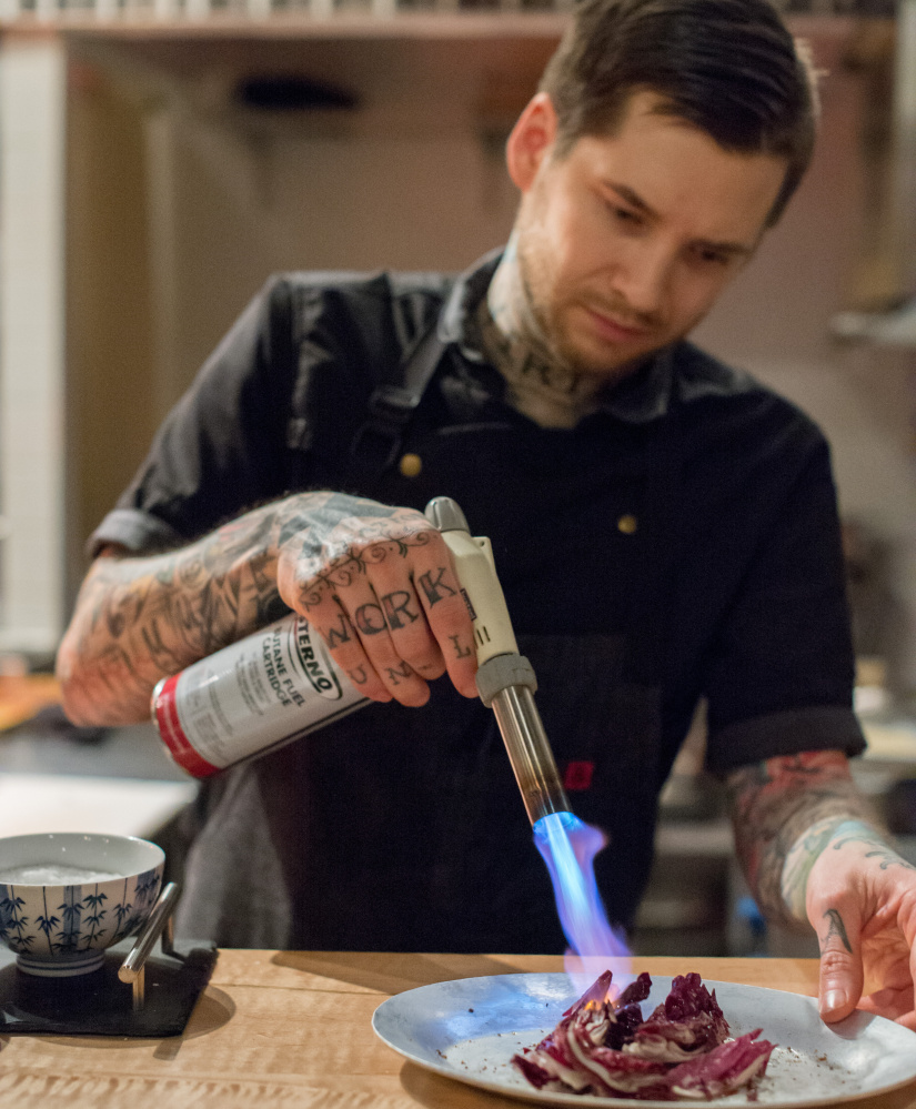 Rocky Hunter, vegetarian chef de cuisine at David's Opus Ten, uses a torch to char radicchio.  Photo by Jordan Moody for Brea McDonald Photography