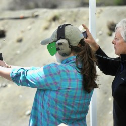 Abigail Hammond of Lincolnville takes aim at a target while Sheri Oldham, a Maine Registered Guide, monitors a timer during a shooting competition held last weekend at the Rangeley Region Guides and Sportsmen's Association.