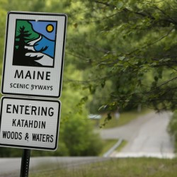 A sign near the north entrance to Baxter State Park along Grand Lake Road indicates the start of a scenic byway connected with the Katahdin Woods & Waters recreation area.