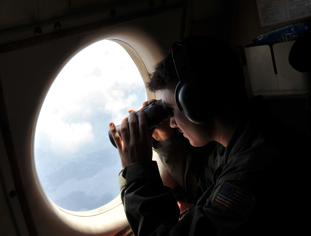 U.S. Navy Lt. j.g. Dylon Porlas looks out from a Lockheed P-3C Orion patrol aircraft Sunday over the area where the EgyptAir flight crashed.