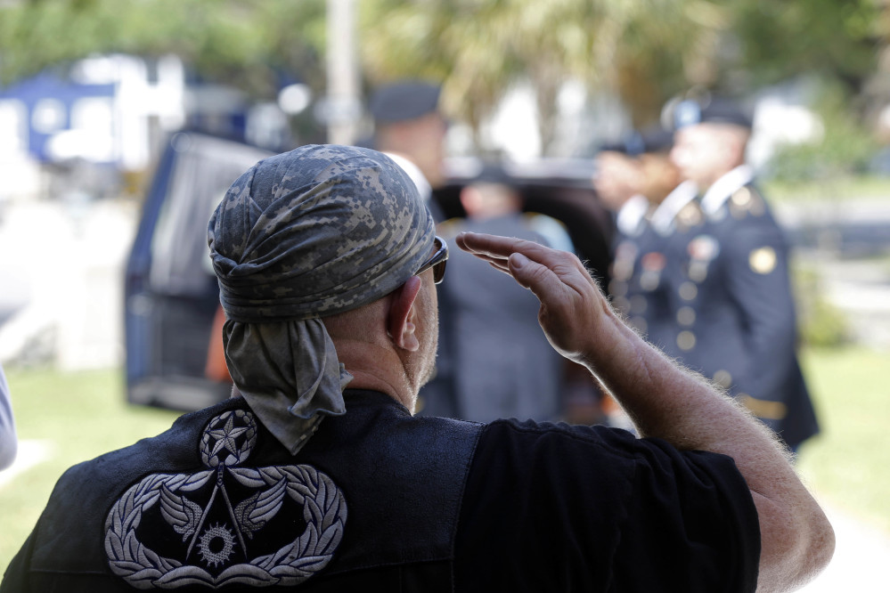 Chuck Gill, of Albany, La., representing the Patriot Guard Riders, salutes as the casket containing remains of Army Pvt. Earl Joseph Keating as it arrives at the Schoen Funeral Home in New Orleans on Monday.