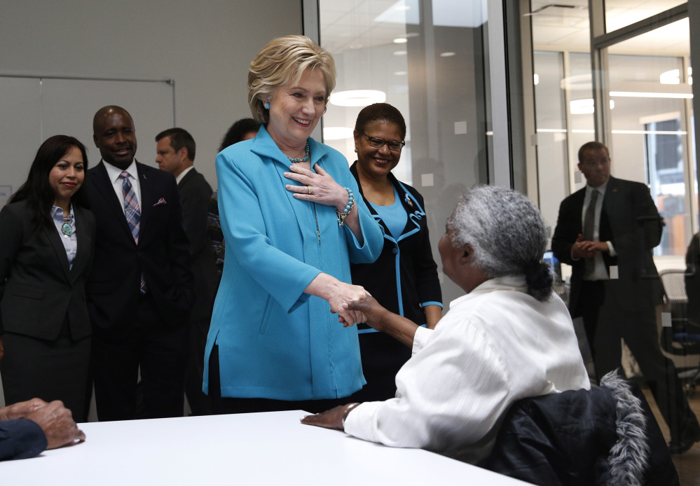 Democratic presidential candidate Hillary Clinton greets people as she tours the Community Coalition on Tuesday in Los Angeles, Calif.