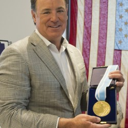 Jim Craig, the hockey goaltender who helped the U.S. win a miraculous gold medal at the 1980 winter Olympics, is framed by a display featuring the jerseys,  skates and goalie equipment he wore in the Soviet and Finland games as well as the iconic American flag that was draped over his shoulders after the gold medal win. Craig is now auctioning off the items.    The Associated Press
