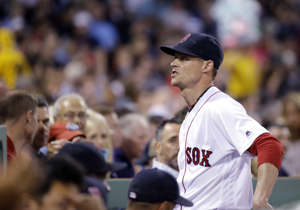 Red Sox starter Clay Buchholz says something to fans as he walks into the dugout after the fifth inning of Thursday's game at Fenway Park against the Colorado Rockies.