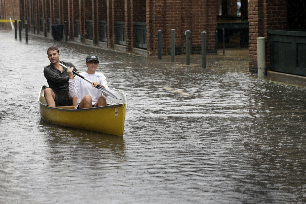 Dillon Christ, front, and Kyle Barnell paddle their canoe down a flooded street in Charleston, S.C., in 2015. During hurricane season, coastal living comes with significant risks.