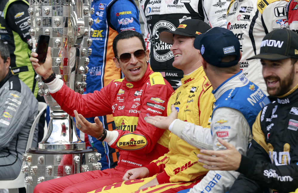 Helio Castroneves, left, jokes with Ryan Hunter-Reay, center, and Tony Kanaan while a photo of the starting field is taken Friday before the final practice session for the Indianapolis 500 at Indianapolis Motor Speedway.