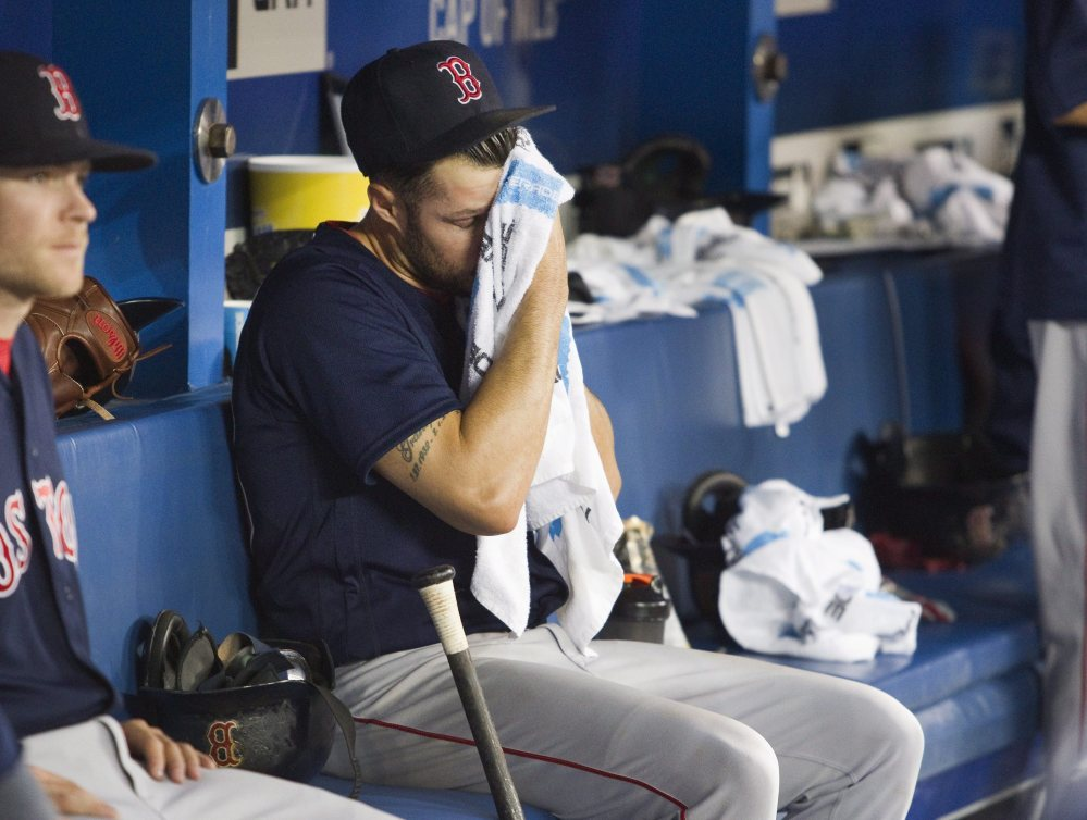 Red Sox starter Joe Kelly sits in the dugout in the fifth inning after being taken out of Friday's game against the Blue Jays at Toronto.