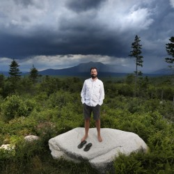 Lucas St. Clair poses on land proposed for a national park in Penobscot County. Mount Katahdin, the state's highest peak, can be seen in the background. St. Clair manages a nonprofit foundation set up to promote the creation of a park on about 70,000 acres owned by his mother, Burt's Bees founder Roxanne Quimby.