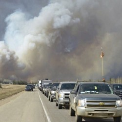 Smoke fills the air as people drive on a road in Fort McMurray, Alberta, Tuesday.The northern Alberta city was ordered evacuated Tuesday as a wildfire whipped by winds engulfed homes and sent ash raining down on residents.