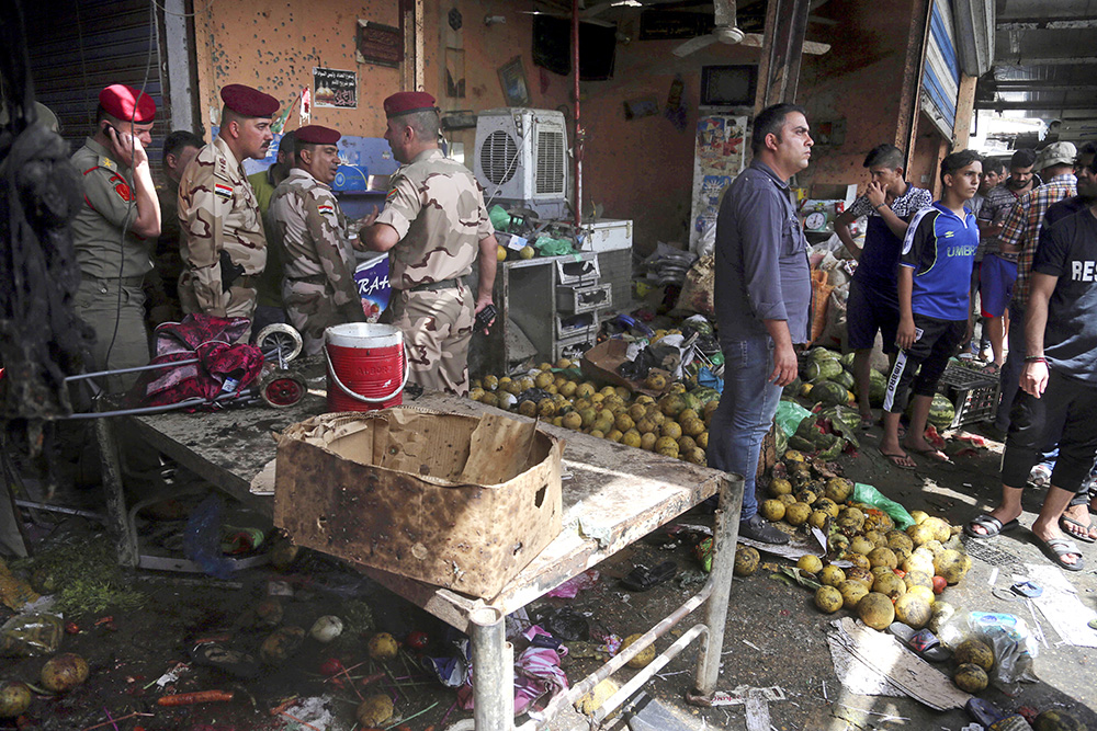 Security forces and citizens inspect the scene after a bomb exploded at an outdoor market in Baghdad's northern neighborhood of Shaab, Iraq, Tuesday. The Associated Press