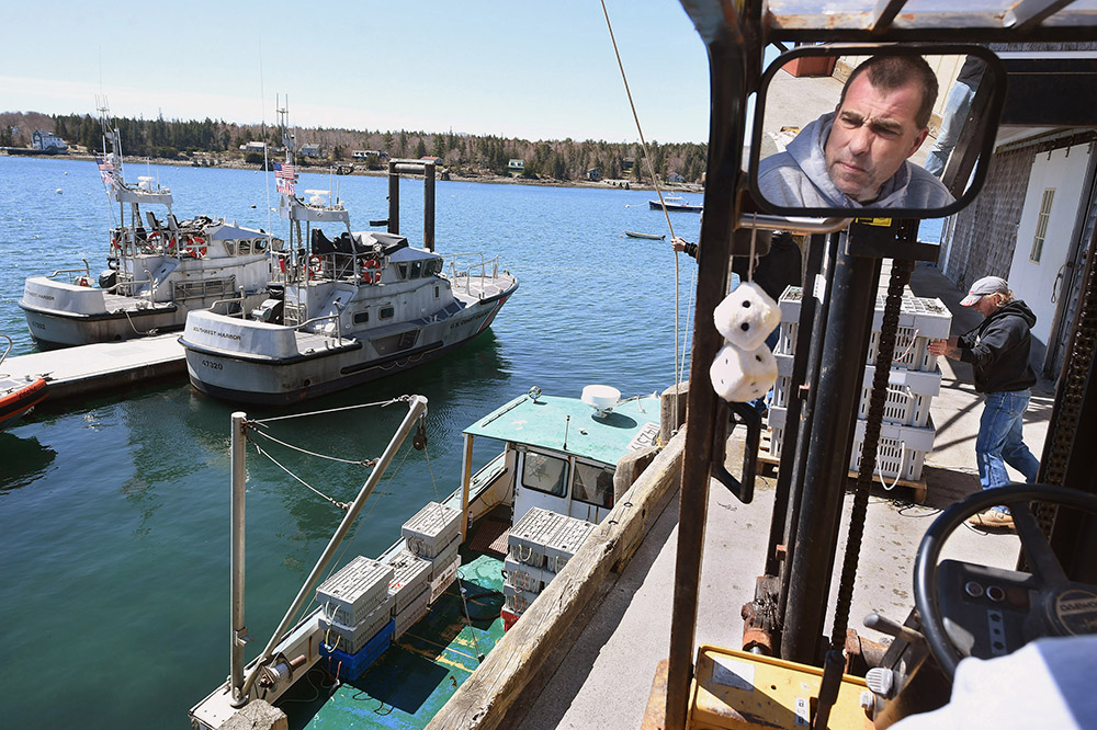 Aaron Bernstein is reflected in a mirror as he and Brian Bunker work on unloading a boat with lobsters recently from Cranberry Isles Fishermen's Co-op at Beal's Lobster Pier. They were to be picked up by Southwest Harbor's Ready Seafood  to begin their journey to China. Photo by Matt McClain/The Washington Post