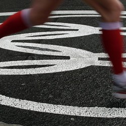 An athlete crosses Olympics Rings on the pavement as she runs in the women's marathon at the 2012 Summer Olympics on, Sunday, Aug. 5, 2012 in London. (AP Photo/Charlie Riedel)