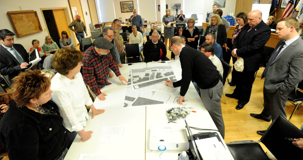 Neil Kitterige , right, draws on a map of Waterville to delineate areas of construction during a meeting at Waterville city council chambers on April 14.