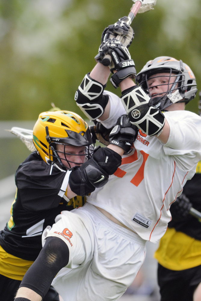 Gardiner's Sloan Berthiaume, right, scores while getting hit by Maranacook's Drew Davis during a lacrosse game Wednesday in Gardiner.