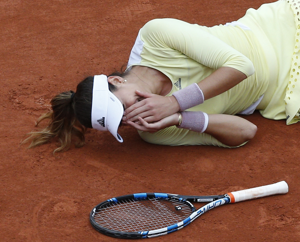 Garbine Muguruza lies on the clay after defeating Serena Williams in the French Open finals Saturday in Paris.