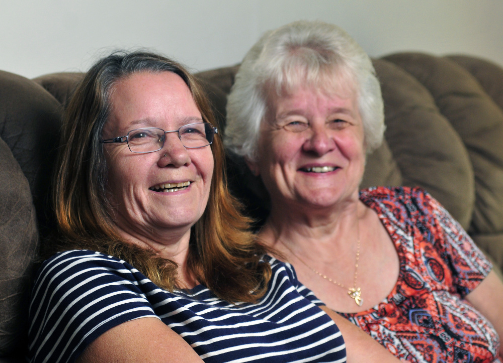 Sisters Jane McDougal, left, and Betty Bickford pose for a portrait Thursday in Sidney. They were separated at birth when McDougal was put up for adoption. McDougal found Bickford about two years ago.