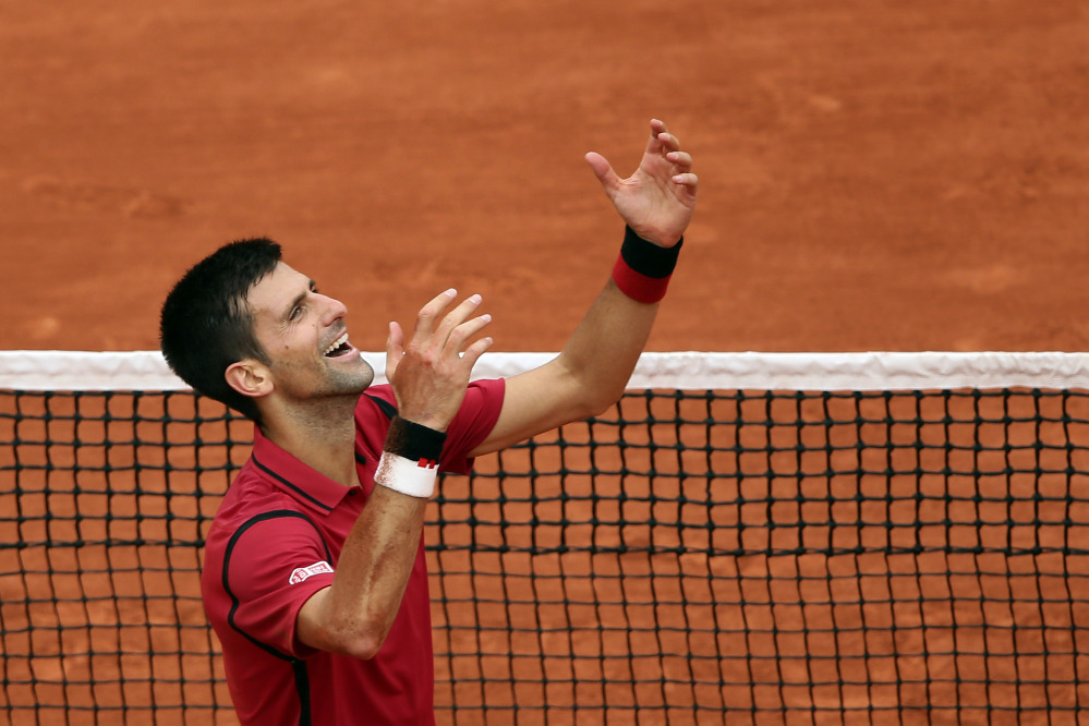 Novak Djokovic raises his arms after defeating Andy Murray 3-6, 6-1, 6-2, 6-4 in the men's final at the French Open on Sunday at the Roland Garros stadium in Paris.