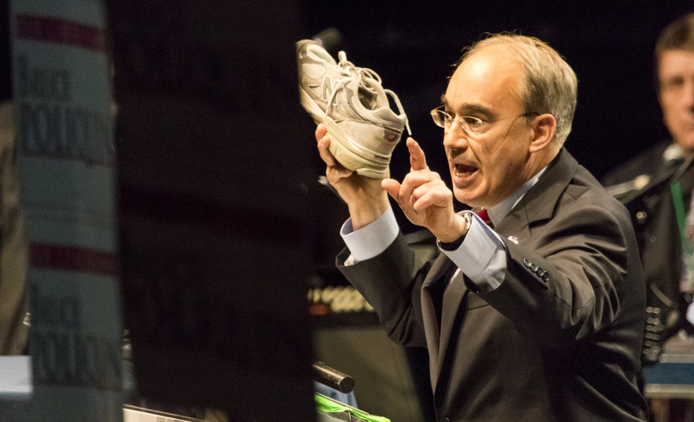 U.S. Rep. Bruce Poliquin, R-2nd District, a keynote speaker during the second day of the Maine Republican Party's state convention at the Cross Insurance Arena in Bangor, holds aloft a New Balance sneaker while calling for changes to the Berry amendment that would favor U.S. made sneakers for military personnel.