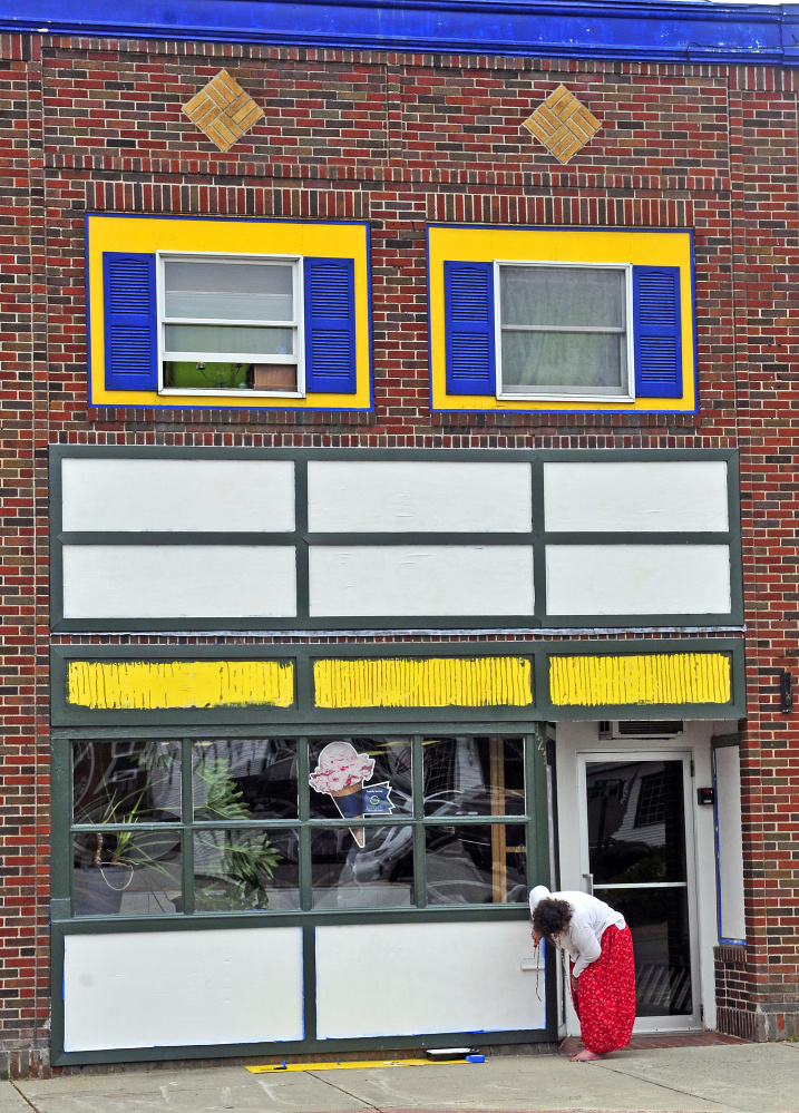 Suzi Brackin paints white over the old yellow and blue facade last week at the former Apple Valley Books that will soon be the site of Coffee & Cones on Main Street in Winthrop.
