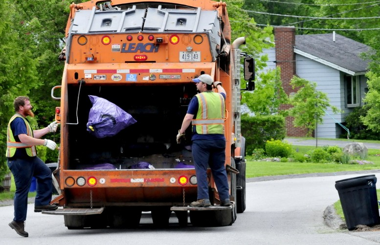 Waterville Public Works employees pick up trash in 2015 in the city. Waterville officials have decided against signing on with a proposed waste-to-energy plant planned for Hampden and instead will send city trash to the Crossroads landfill in Norridgewock for the next five years.