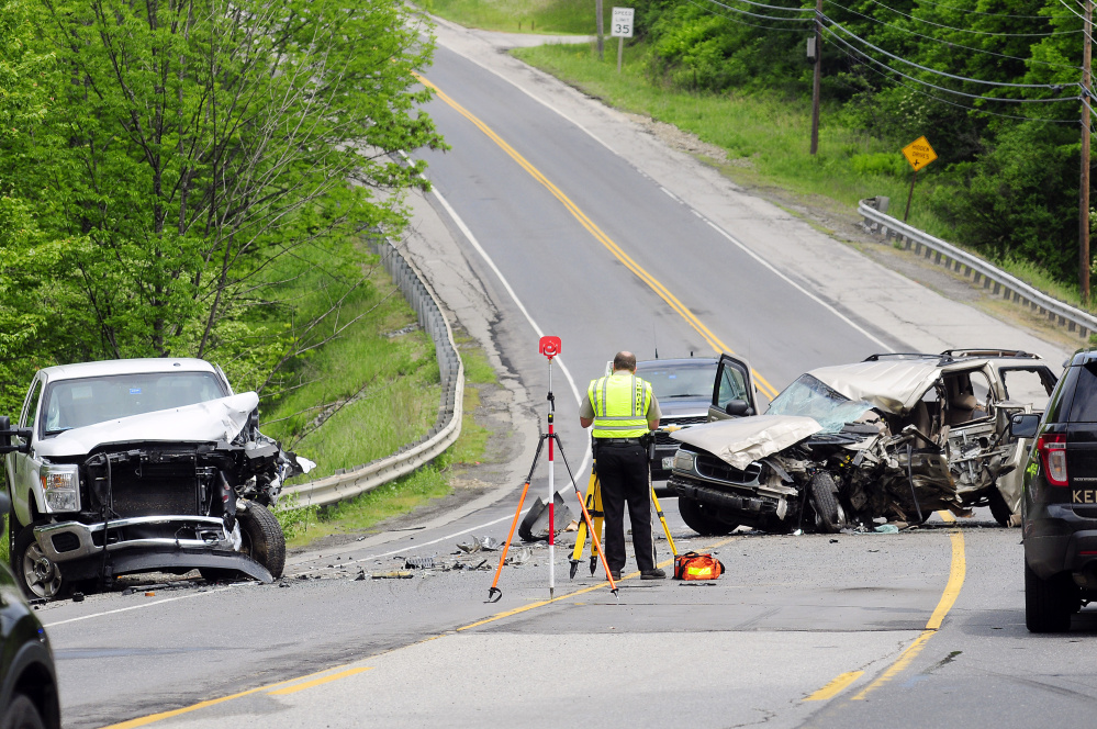 Officials work at the scene of a fatal two-vehicle crash on Tuesday on Western Avenue, also called U.S. Route 202, in Manchester near the Augusta line.