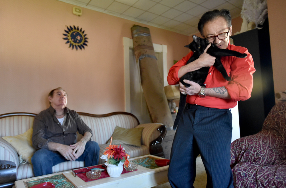 Aldo Baldie cuddles with his cats, Mother Mary and Saint Joseph, at his new apartment with his husband, Ron Pelletier, on the couch in the background in April. The couple lost seven pets when their Canaan home was burned in an arson in September. Matthew Short, of Canaan, pleaded guilty Tuesday.
