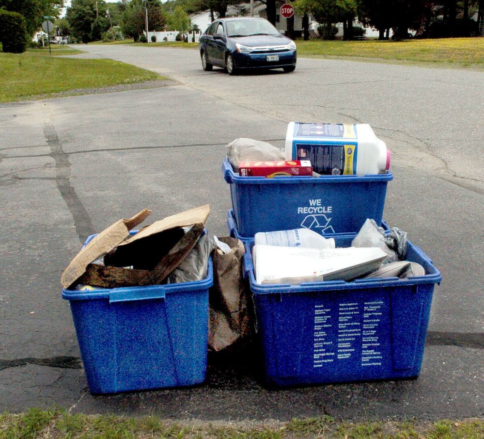 Recycling containers await pickup Thursday in Madison. Town residents will vote Monday at Town Meeting on a proposal to eliminate curbside recycling.