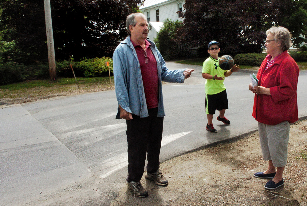 Norridgewock Upper Main Street residents Butch and Cheri White and their grandson Parker, standing near the speed hump on Monday, say they support the raised pavement beside their home and that it slows down drivers in the neighborhood.