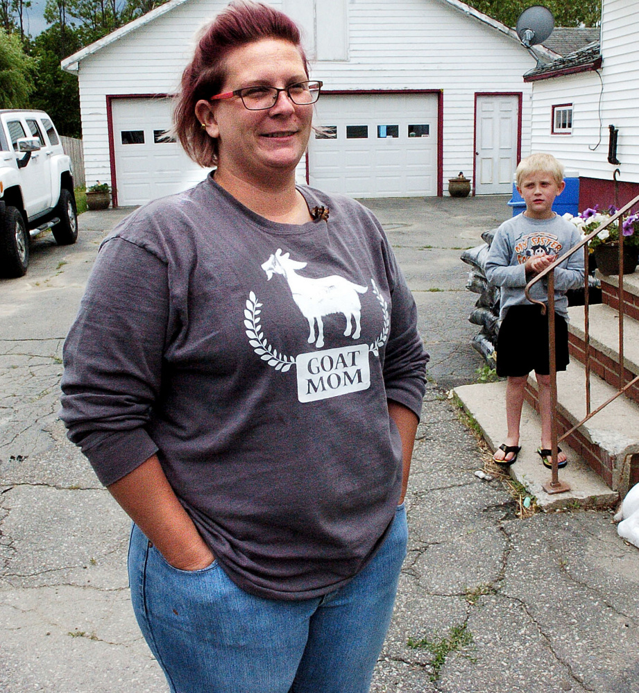 Emily Smith speaks in favor of the speed hump that slows traffic near her home on Upper Main Street in Norridgewock on Monday. In background is her son Slater, who along with his brothers, is not allowed close to the street.