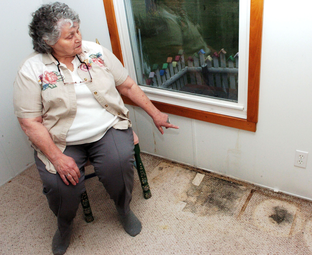 Jan Martin points to where water has seeped inside from a window and contributed to black mold on the carpet in May in a room of her home in Skowhegan. After a Morning Sentinel column publicized the issue and Martin's difficulty getting help, she has received and outpouring of support.