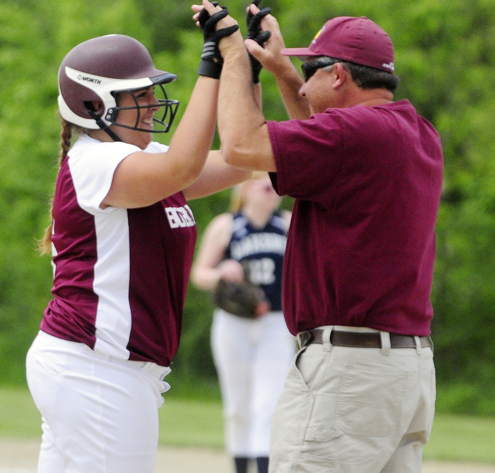 Richmond's Emily Douin, left, celebrates with coach Tony Martin after hitting a two-run triple in the third inning of a Class D South semifinal Friday against Greenville in Richmond.