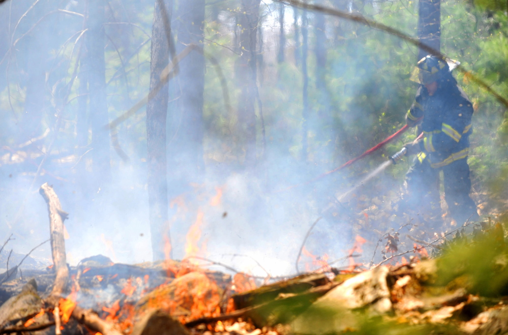 Jonathan Berringer, a firefighter with the Winslow fire department, battles a grass fire on Morrill Road in Winslow in May 2015. Fire departments across central Maine said Monday that drier than normal conditions mean a high fire danger.