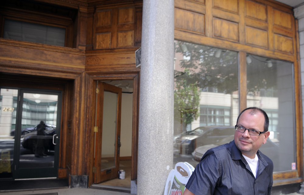 University of Maine at Augusta art professor Peter Precourt stands on Tuesday outside the space he plans to open as a temporary art gallery at 265 Water St. in Augusta.