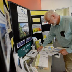 David Woodsmen, state senator from Sanford, picks up pieces of solar power literature before speaking Thursday at The Future of Solar in Maine Forum at Colby College in Waterville.