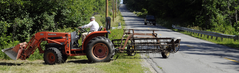 Brian Luce tends to hay Sunday on a family field in Sidney after crossing the Mill Pond Bridge on Middle Road. The Maine Department of Transportation is proposing to replace the structure.