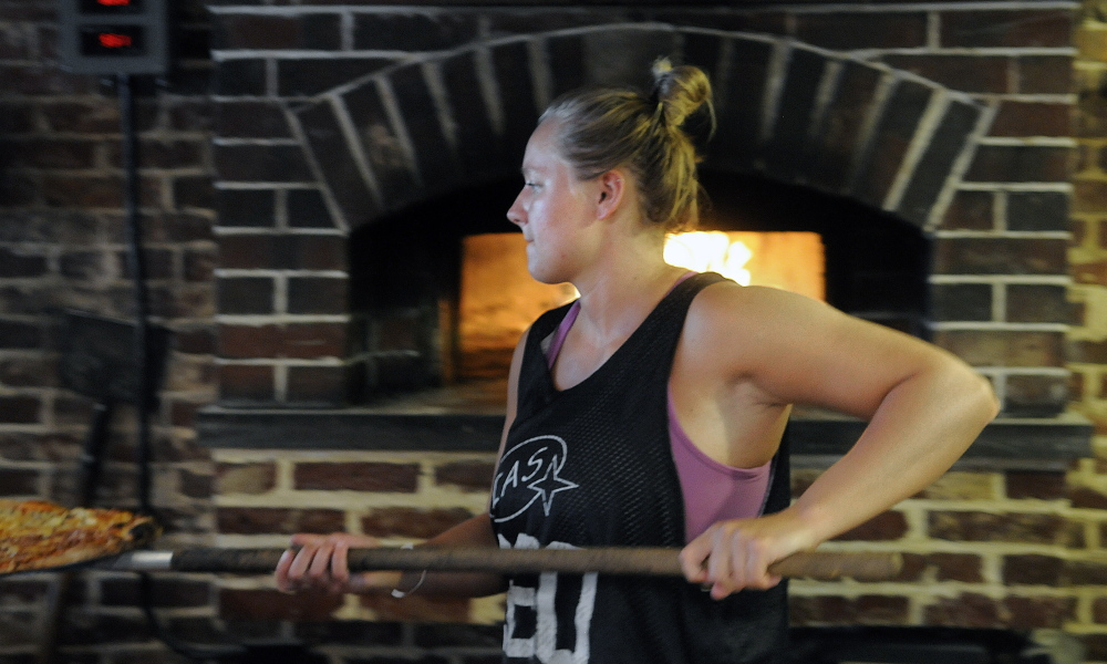 Kaylee Heath serves a pizza she baked on Aug. 17, 2015, in the brick oven at Kennebec Pizza in Hallowell. The Water Street business is scheduled to reopen soon under the new ownership of Kevin Hachey.